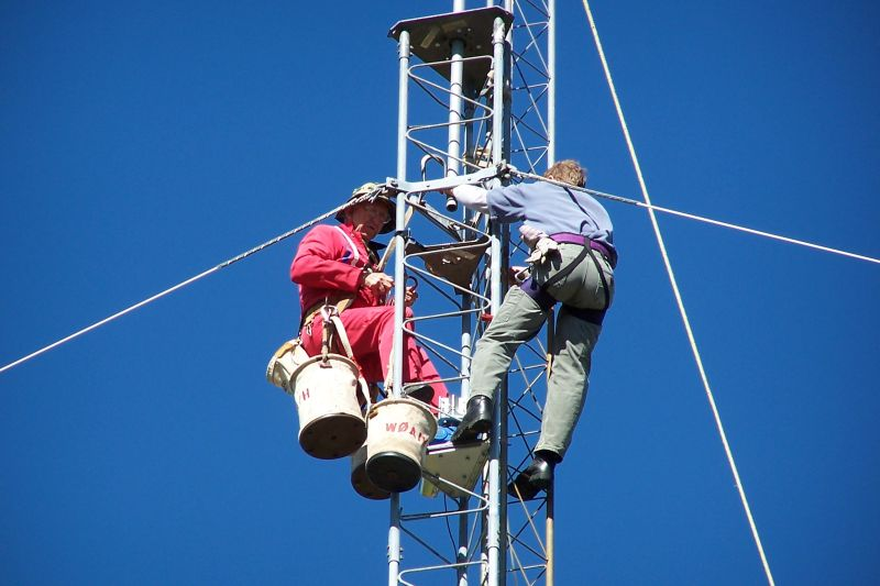 (L-R) Paul WØAIH and Chris KC9DGP working on tower.  Note guy wires are Polygon Fiberglass Rod.  Also note rope going