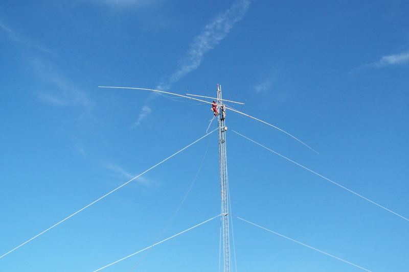WØAIH and KC9DGP attach the Force 12 EF-180C 80m Rotatable Dipole to the mast.  The EF-180C is about 85 feet long.