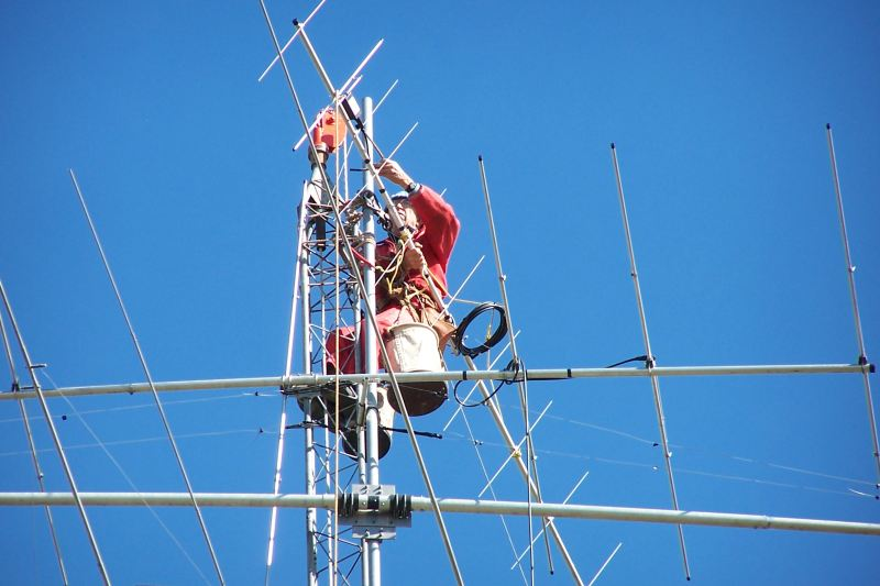 Paul WØAIH mounting 2 meter beam at the top of the mast.  Approximate height is 108 feet.