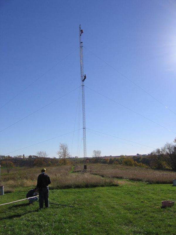 TOWER: Paul WØAIH on the Gin Pole with Chris KC9DGP below. GROUND: (l-r) Scott KA9FOX and Eric KB9TKF prepare 2m antenna for fin