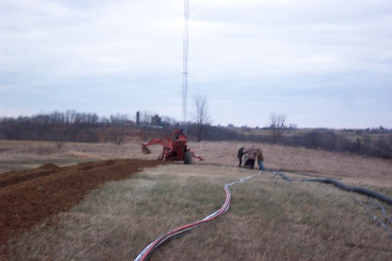Trencher finishes up his work, while ground crew finishes rolling out hardline.